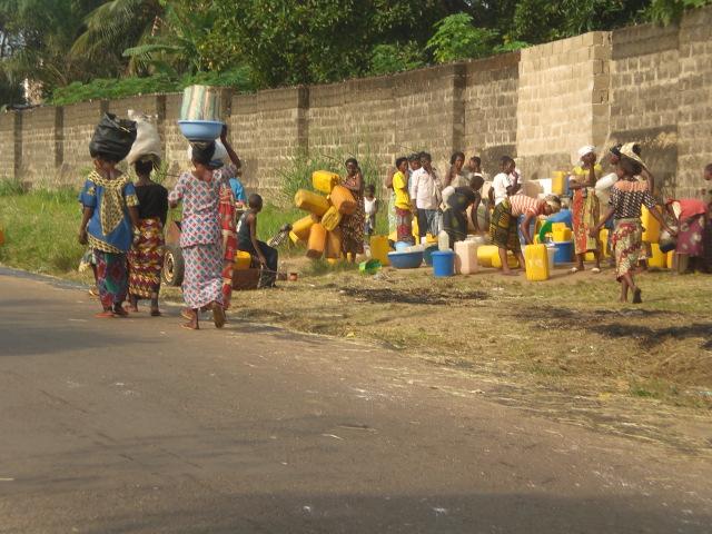 Familias del barrio van por agua al pozo de la escuela en Kimwenza